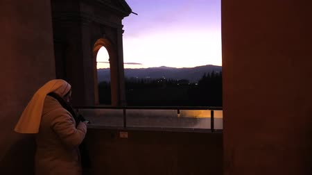 madona : Bologna, Italy - January 12, 2018: Sister looking a winter sunset from Sanctuary of Madonna di San Luca arcades. The church of Blessed Virgin of San Luca is a pilgrimage site of Europe.
