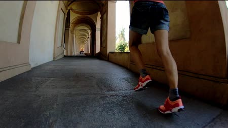 madona : SLOW MOTION: bottom view of sporty legs running in San Lucas archway to the San Luca Sanctuary on Colle della Guardia hill. Bologna city of Italy. Dostupné videozáznamy