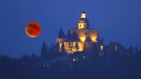 lunar surface : full red moon phases of the lunar eclipse with San Luca basilica church on Bologna hills in Italy by night.