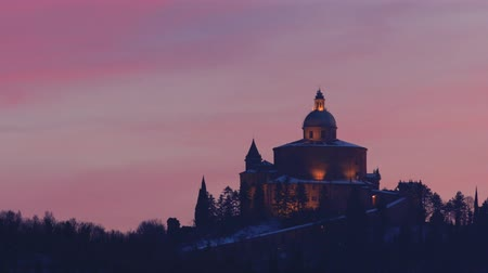 madona : Distant view of Sanctuary of Blessed Virgin of San Luca on Colle della Guardia in Bologna. Twilight in the winter snow, pink sky with Copy space. Historical church and pilgrimage destination in Italy.