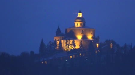 szentelt : San Luca Sanctuary by night in Bologna city. Historical church and pilgrimage destination in Emilia-Romagna, Italy. Stock mozgókép