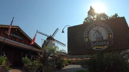 danimarka : Solvang, California, United States - August 10, 2018: Solvang Brewing Company in Solvang Historic Downtown, a Danish Village in Santa Ynez Valley. Sunny day, blue sky. Old windmill on background. Stok Video