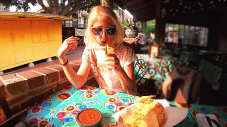food state : SLOW MOTION: El Pueblo de Los Angeles State Historic Landmark, California, United States. Happy tourist woman drinking Margarita. Oldest part of Downtown