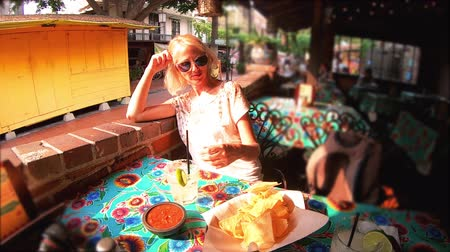 типичный : SLOW MOTION: Happy caucasian woman drinks Margarita, Mexican cocktail based on tequila. El Pueblo in Los Angeles Downtown State Historic Park, California, United States.