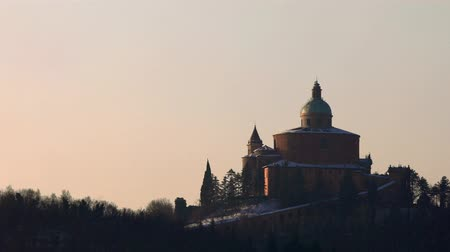 bolognai : San Luca basilica church at dawn with snow in winter and sun rising on Bologna hills in Italy Stock mozgókép
