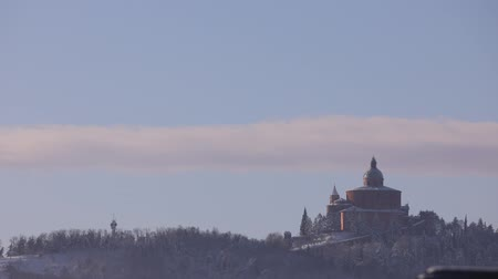 マドンナ : TIME LAPSE: San Luca basilica sanctuary at dawn with snow in winter with sun rising on Bologna hills in Italy. 動画素材