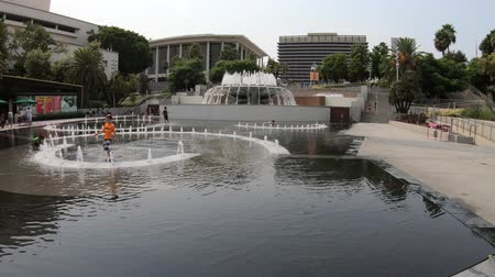 metropolitan area : Los Angeles, California, United States - August 9, 2018: children playing in fountain water at the Grand Park in Downtown of LA. Sunny day in blue sky. Urban summer cityscape. Urban summer season.