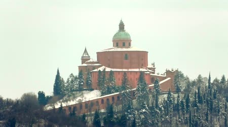 madona : distant close up of snowy San Luca basilica in a winter morning on Bologna hills in Italy.
