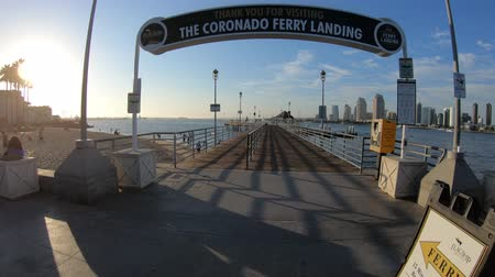 barışçı : San Diego, California, United States - August 1, 2018: Coronado Ferry Landing signboard entrance at old pier in Coronado Island. San Diego downtown skyline in San Diego Bay on background. Blue sky.