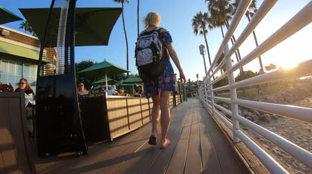 San Diego, United States - August 1, 2018: following woman on wooden boardwalk to covered patio on coastal beach in San Diego Bay from Coronado Island. Summer destination in California West Coast. Стоковые видеозаписи