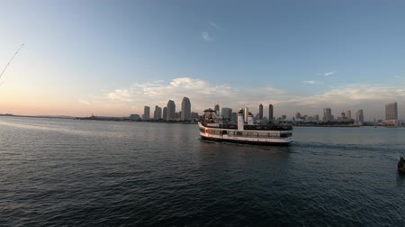 San Diego, California, United States - August 1, 2018: ferry cruise in waters of San Diego Bay with San Diego skyline waterfront marina and urban downtown cityscape at sunset on background.
