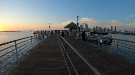 San Diego, United States - August 1, 2018:San Diego Bay sunset on old wooden pier in Coronado Island, California. People and tourists fishing and walking and enjoying the view of San Diego waterfront.
