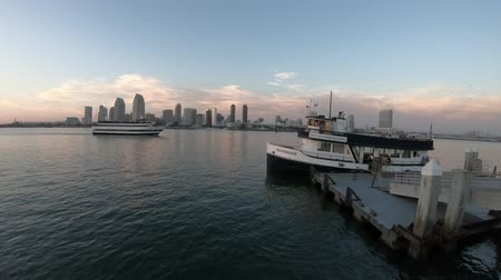 San Diego, United States - August 1, 2018:Scenic sunset view of Coronado Ferry leaving Coronado Island, California. from old wooden pier reflecting in San Diego Bay at twilight.