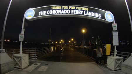 San Diego, California, United States - August 1, 2018: Coronado Ferry Landing signboard entrance at old pier in Coronado Island.San Diego downtown skyline and waterfront marina, San Diego Bay at night