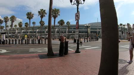 homeless : San Diego, California, United States - July 31, 2018: Homeless looking for food in garbage can in Gaslamp Quarter, San Diego Downtown. Convention Center and Harbor Drive on background. Urban scene.