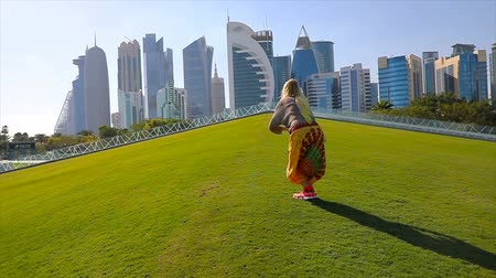 arábie : SLOW MOTION: Happy woman traveler on a green grass jumping open wide with skyscrapers of West Bay. Blonde female tourist enjoys Doha Downtown skyline st sunset. Travel in Qatar, Middle East.