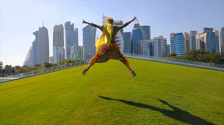 ugró : SLOW MOTION: woman tourist on a green grass jumping by skyscrapers of West Bay. Blonde female tourist enjoys Doha Downtown skyline in a sunny day. Travel in Qatar, Middle East.
