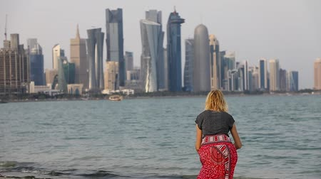 mia : SLOW MOTION: Caucasian woman jumping on the Doha West Bay in Qatar. Blonde tourist enjoys Doha Downtown from West Mound-Skyline viewpoint. Persian Gulf, Middle East, Arabian Peninsula.
