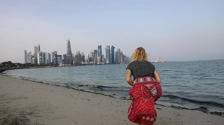 沿岸の : SLOW MOTION: Back of caucasian woman jumping on the beach with the modern skyscrapers of Doha West Bay along Corniche promenade on Doha Bay in a sunny day. Qatar, Arabian Peninsula in Persian Gulf.
