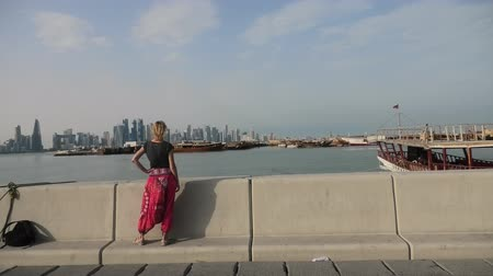 enjoys : Happy caucasian woman relaxing along Corniche promenade with Dhow Harbour and Doha West Bay skyline on background. Lifestyle tourist enjoys in Doha city, Qatar, Middle East, Arabian Gulf. Stock Footage