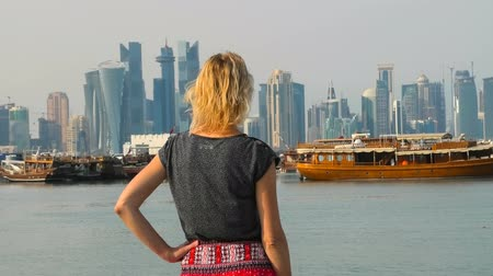 mia : Happy woman backside relaxing on seafront of Doha park along Doha Bay with traditional dhow. Lifestyle tourist at East Mound-Skyline view skyscrapers of Doha Downtown.Qatar, Middle East, Persian Gulf Stock Footage