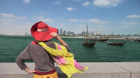 mia : Qatar travel concept. Elegant caucasian woman enjoyis the views of Doha West Bay. Blonde tourist at Doha Downtown from East Mound-Skyline viewpoint. Persian Gulf, Middle East, Arabian Peninsula.
