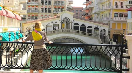 pearl : Blonde woman on balcony looking canals of Venice in Doha Qatar. Caucasian tourist enjoys Qanat Quartier in the Pearl-Qatar, Persian Gulf, Middle East, Persian Gulf. Sunny day with blue sky.