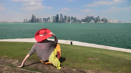lugar famoso : Caucasian woman sitting on green lawn looks at the views of Doha West Bay in Qatar. Blonde tourist enjoys Doha Downtown from West Mound-Skyline viewpoint. Persian Gulf, Middle East, Arabian Peninsula.