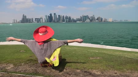 mia : Caucasian woman backside with open arms sitting on green lawn of Doha West Bay in Qatar. Blonde tourist enjoys Doha Downtown from West Mound-Skyline viewpoint. Persian Gulf, Arabian Peninsula.