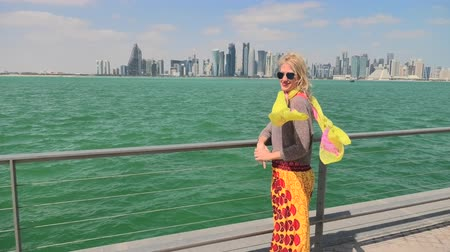 西 : Happy woman along the Doha Bay looking cityscape on background. Lifestyle caucasian tourist enjoys skyscrapers of Doha Downtown skyline. Qatar, Middle East travel concept.