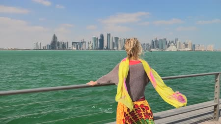middle : Carefree woman enjoys the seascape of Corniche promenade of Doha Bay in Qatar. Lifestyle caucasian tourist looking at the skyscrapers of Doha Downtown skyline.