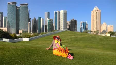 lugar famoso : Travel in Qatar, Middle East. Happy woman in sunhat sitting on a green lawn in a park with modern skyscrapers of West Bay on background. Female tourist enjoys Doha Downtown skyline.
