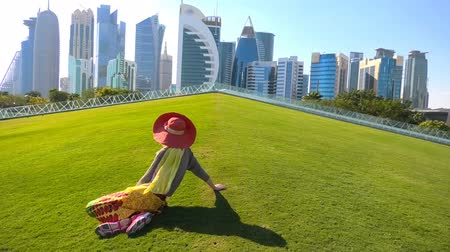 sunhat : Woman backside with sunhat sitting on a green lawn in a park with skyscrapers of West Bay on background. Female tourist enjoys Doha Downtown skyline in a sunny day. Travel in Qatar, Middle East.