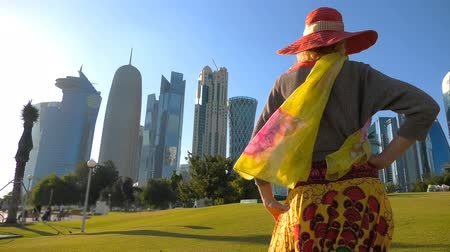 sunhat : Woman tourist close up with sunhat on a green lawn in a park with skyscrapers of West Bay on background. Tourist enjoys Doha Downtown skyline in a sunny day. Travel in Qatar, Middle East.
