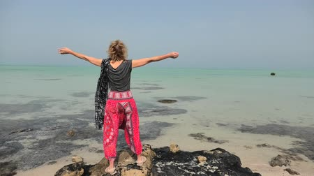enjoys : Caucasian woman with raised arms looking at the Al Thakira Mangroves Nature Reserve in Al Dhakira, a popular touristic attraction. Happy blonde tourist visits Qatar in Middle East, Persian Gulf. Stock Footage