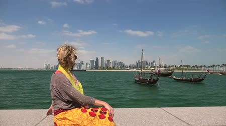 mia : Happy woman on seafront of Doha park along Doha Bay with traditional dhow on background. Lifestyle caucasian tourist enjoys East Mound-Skyline view skyscrapers of Doha Downtown. Qatar, Middle East. Stock Footage