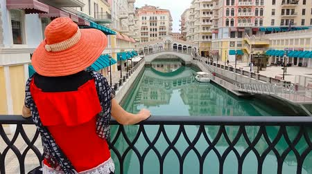 sunhat : Tourism in Qatar.Portrait of woman looking at famous bridge reflecting on waters of canals in scenic Venice Doha city. Caucasian tourist at Qanat Quartier in the Pearl-Qatar, Persian Gulf, Middle East