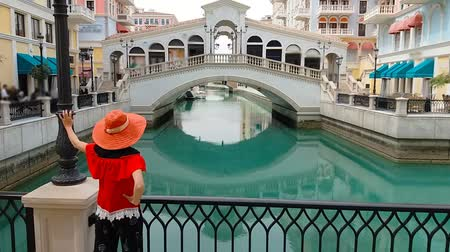 erkély : Woman standing on balcony looking famous bridge of Venice, Doha Qatar, at twilight. Caucasian tourist at Qanat Quartier in the Pearl-Qatar, Persian Gulf, Middle East. Travel in Arabian Peninsula.