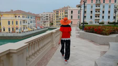 sunhat : Tourism in Qatar. Happy lifestyle woman in sunhat walking by canals in Venice Doha city. Blonde tourist at Qanat Quartier in the Pearl-Qatar, Persian Gulf, Middle East. Stock Footage