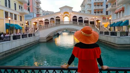 perzisch : Back of woman on balcony looking famous bridge of Venice, a Venetian style waterfront village at sunset. Caucasian tourist at Qanat Quartier in the Pearl-Qatar, icon of Doha, Persian Gulf, Middle East