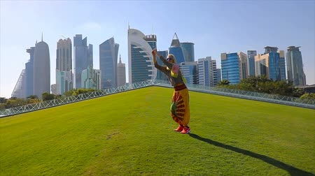 leaping : SLOW MOTION: Happy woman traveler on a green park jumping with skyscrapers of West Bay on background. Blonde female tourist enjoys Doha Downtown skyline in a sunny day. Travel in Qatar, Middle East.