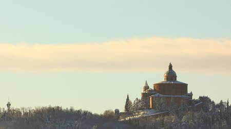 oszlopsor : TIME LAPSE: San Luca basilica sanctuary at dawn with snow in winter with sun rising on Bologna hills in Italy. Stock mozgókép