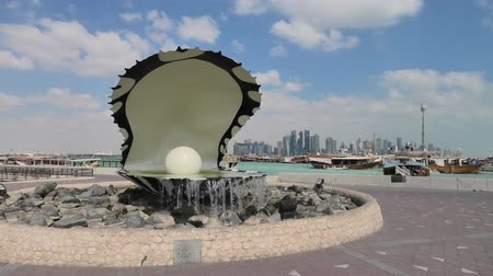 oysters : Doha, Qatar - February 23, 2019: Oyster and Pearl Monument with fountain, celebrates the past pearl industry in Qatar. Corniche seaside promenade at beginning of Dhow Harbor.