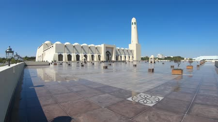 grand mosque : Scenic Doha Grand Mosque with a minaret at sun light reflecting on the outdoor pavement. Qatar State Mosque, Middle East, Arabian Peninsula in Persian Gulf. Stock Footage