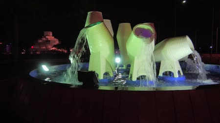 mia : Doha, Qatar - February 16, 2019: water pots fountain or jar fountain on the Corniche promenade and Dhow Harbor with the distant Museum of Islamic Art. West Bay skyline illuminated at night.