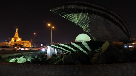 mosque doha : Doha, Qatar - February 23, 2019: TIMELAPSE of famous Oyster and Pearl Monument with fountain on Corniche at beginning of Dhow Harbor. Fanar Islamic Cultural Center illuminated at night on background.