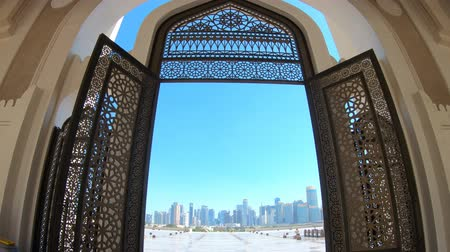grand mosque : Modern skyscrapers of Doha West Bay skyline view from State Grand Mosque in Doha, Qatar, Middle East, Arabian Peninsula. Door of entrance at Mosque in Arabian style. Stock Footage