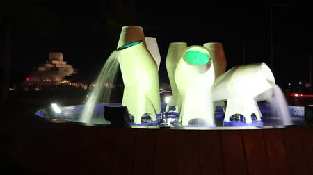 mia : Doha, Qatar - February 16, 2019: TIMELAPSE water pots fountain or jar fountain on the Corniche promenade with Museum of Islamic Art and museum park with palm trees illuminated at night on background.