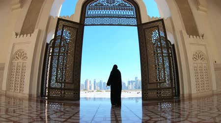 entrance : Woman with abaya dress looks at views of skyscrapers of Doha West Bay skyline outdoors State Grand Mosque in Doha, Qatar, Middle East, Arabian Peninsula. Stock Footage