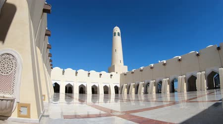 минарет : Doha, Qatar - February 21, 2019: panoramic courtyard with minaret and domes reflecting in sunny day. Imam Abdul Wahhab Mosque or Qatar State Mosque in Middle East. The Grand Mosque is in West Bay.